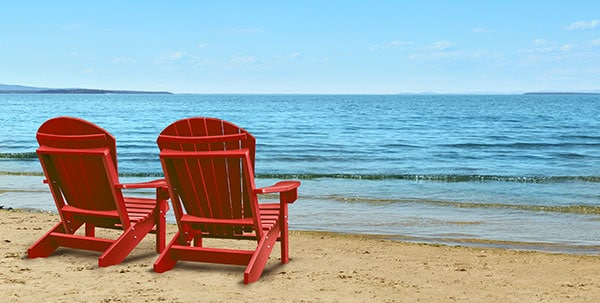 This image represents retirement. Two Adirondack chairs sitting in the sand at the beach facing the ocean.