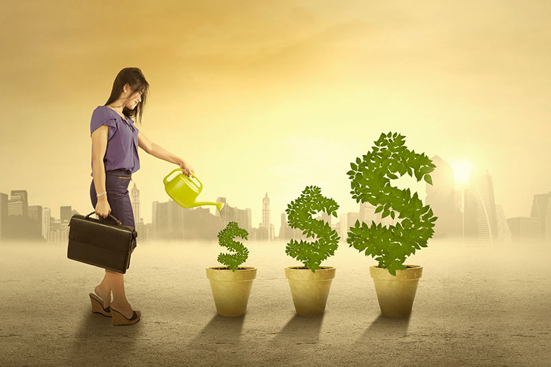 Shows a professional woman watering flower pots. The pots are growing ever-larger dollar signs instead of plants.