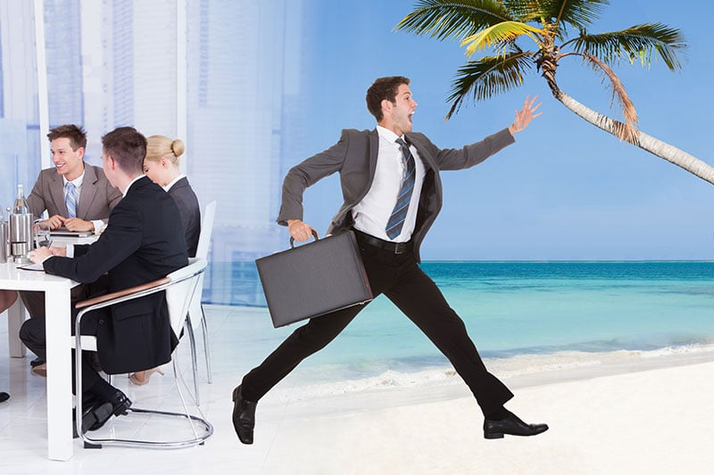 Becoming financially free from your job is represented by a business man running to the beach.